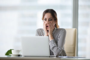Business woman receives unexpected bad news on her laptop